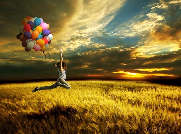 Donna lbera vola con palloncini campo di grano