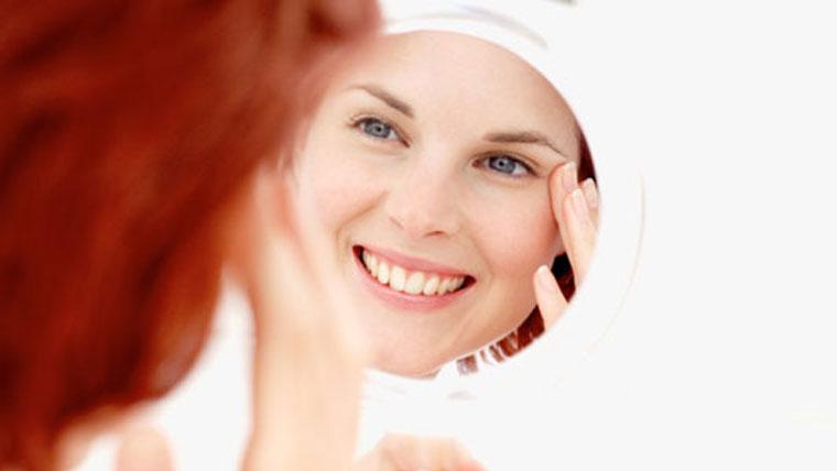 Viso di una donna riflesso nello specchio