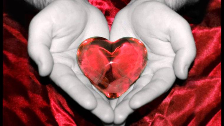 Cuore di cristallo rosso tra e mani