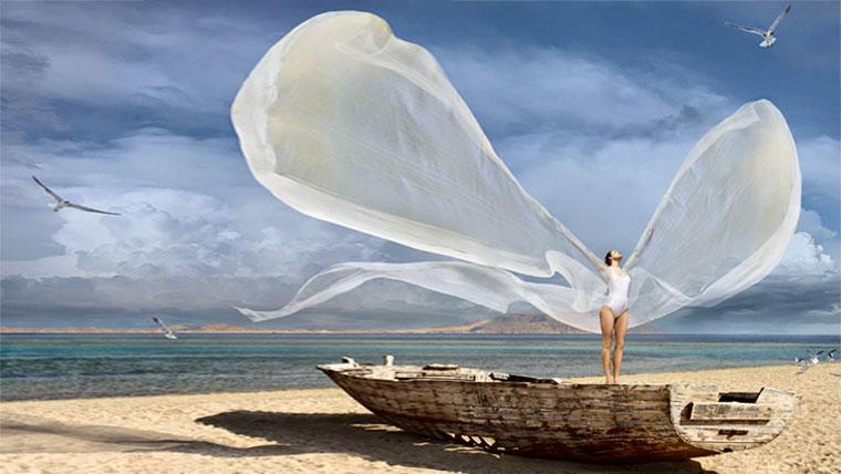 Donna coraggiosa in riva al mare con ali spiegate