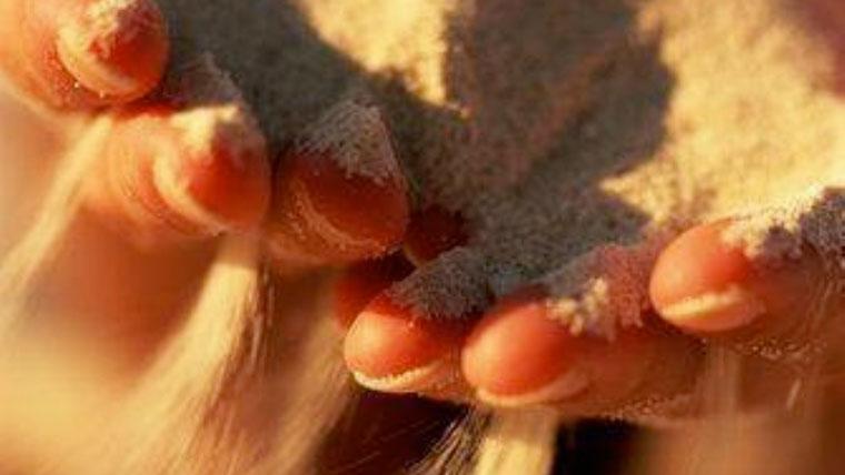Granelli di sabbia che scorrono tra le dita