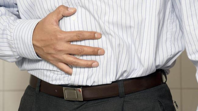 Uomo con problemi digestivi stringe la pancia con una mano