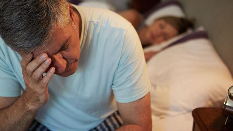 Uomo a letto disperato con una mano sul viso