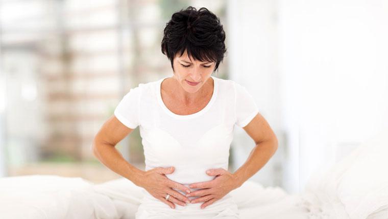 Donna con le mani sul ventre prova dolore a causa del pavimento pelvico contratto