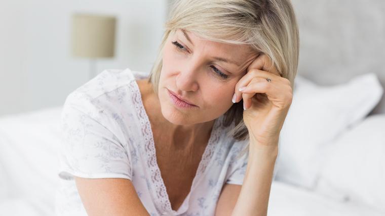 Tossine accumulate peggiornano la situazione di una donna pensierosa seduta sul letto